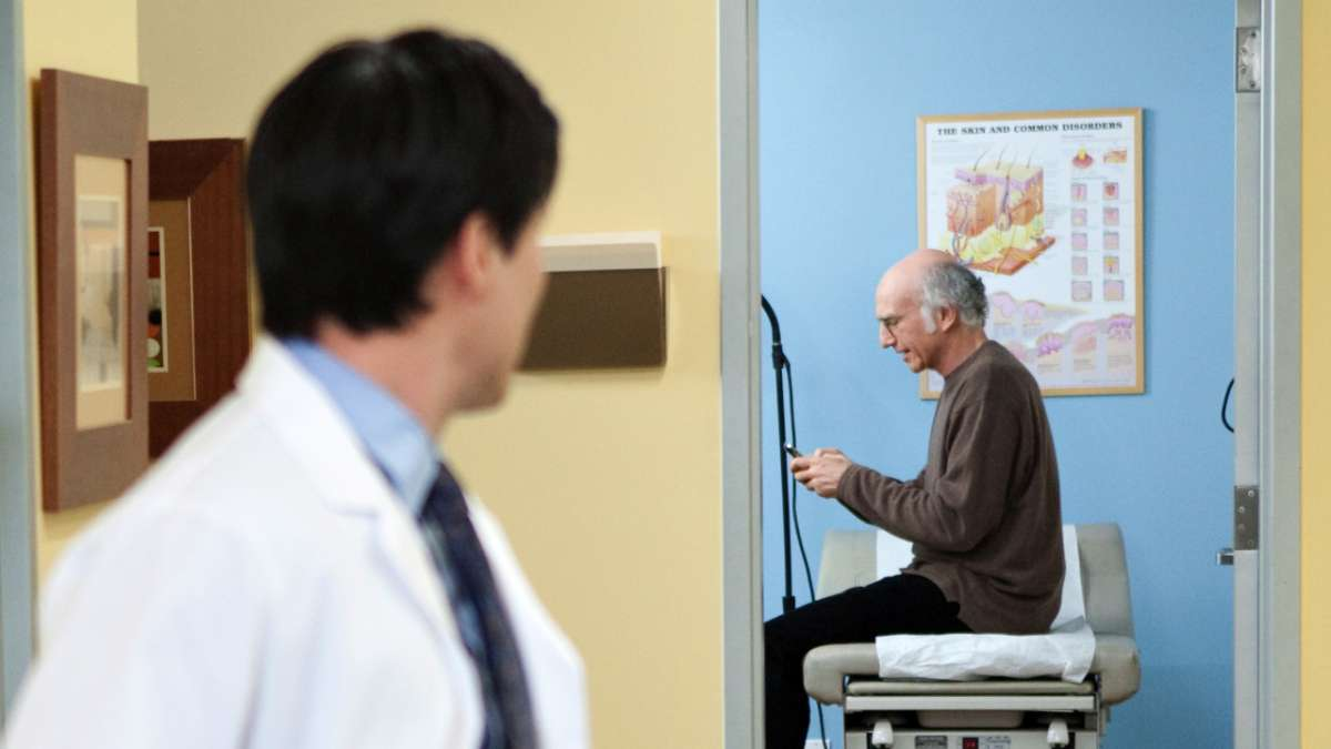 Doctor looking at Larry David texting in examination room
