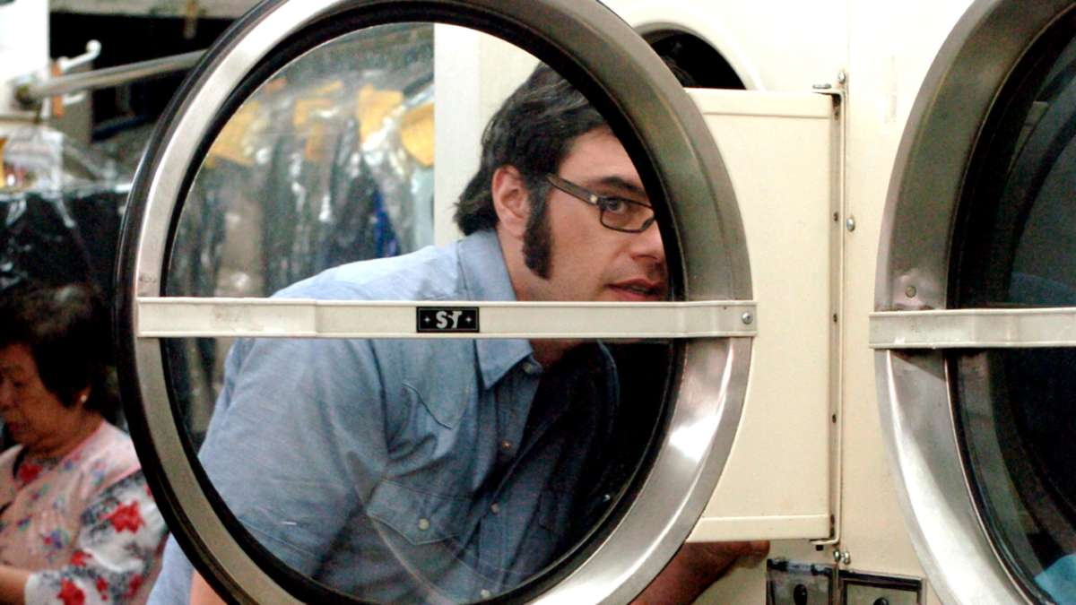 Jermaine spies from behind washer door