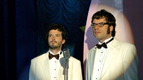 Bret and Jermaine standing in spotlight in white tuxedos