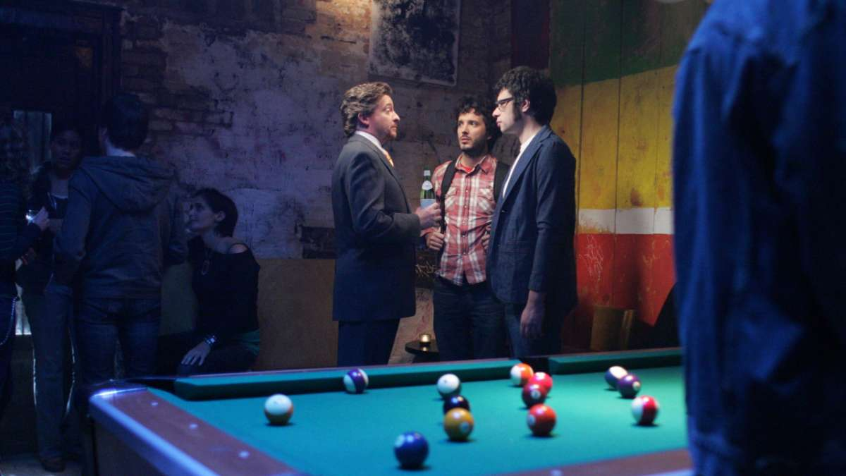 Murray Bret and Jemaine talk beside pool table