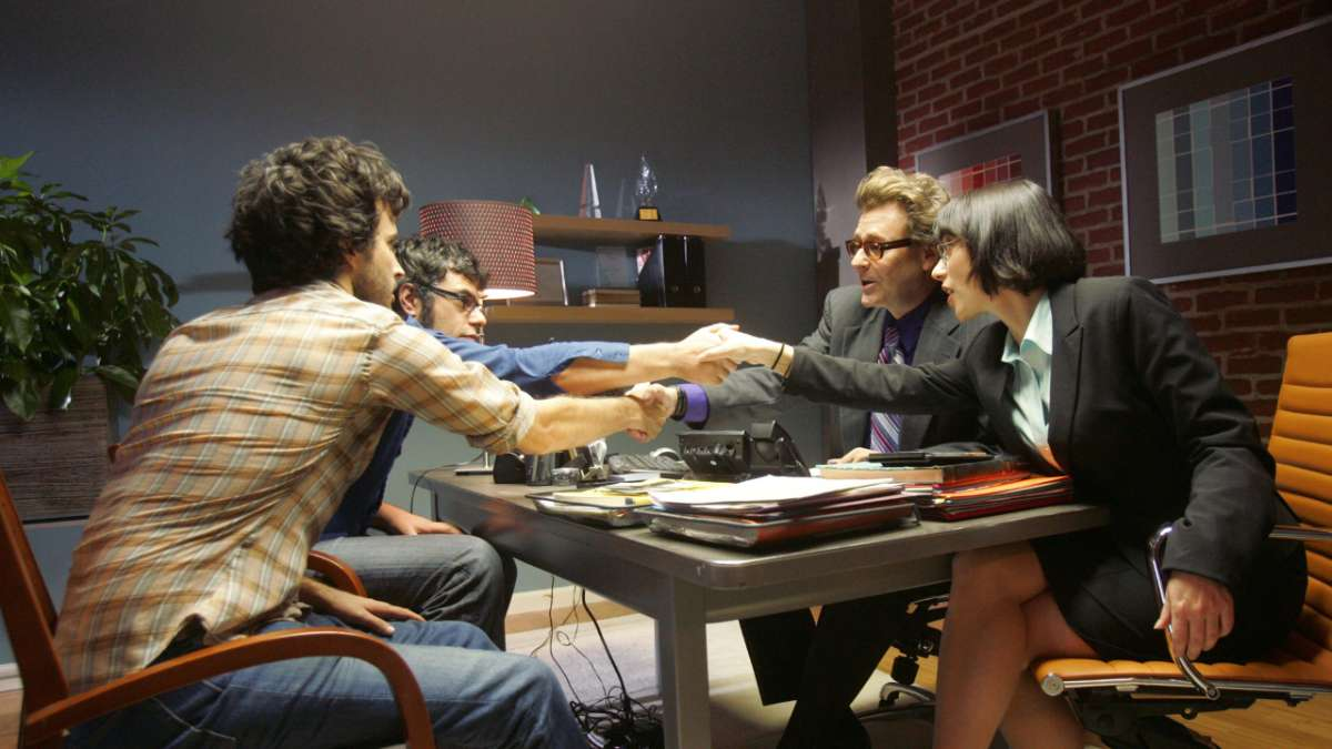 Bret and Jemaine shake hands with executives at desk