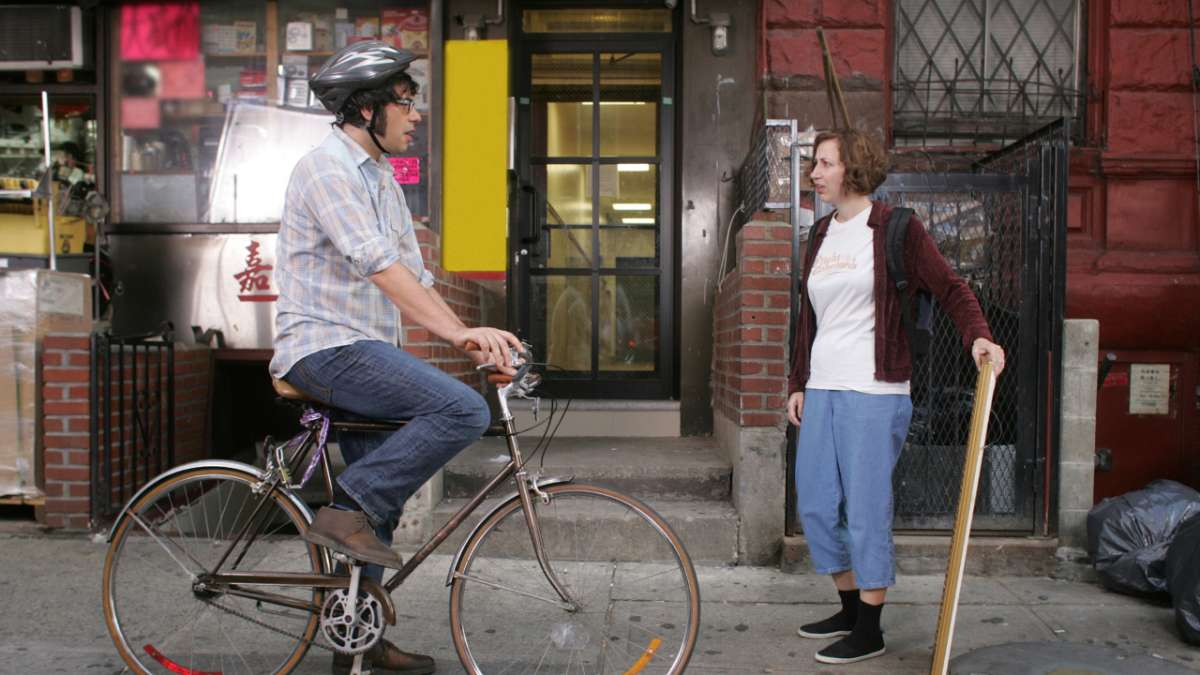 Jemaine on bike speaks to Mel on street
