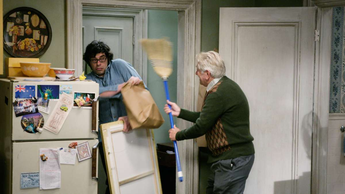 Old man attacks Jemaine with broom in kitchen