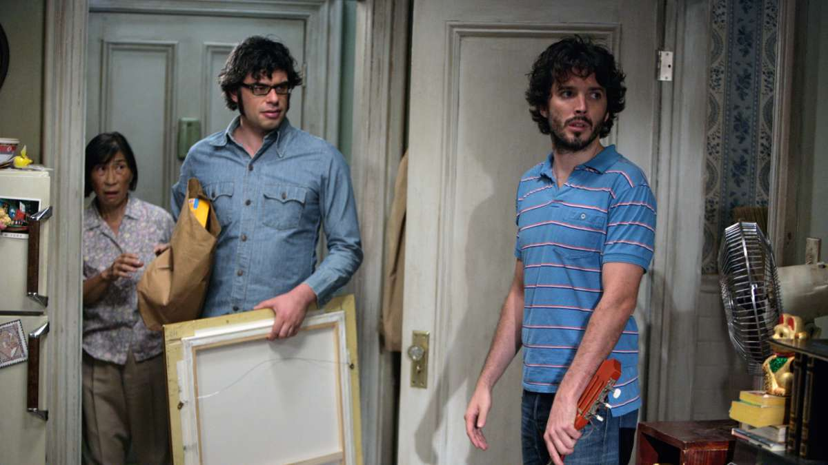 Jemaine and Bret in kitchen with old woman in background
