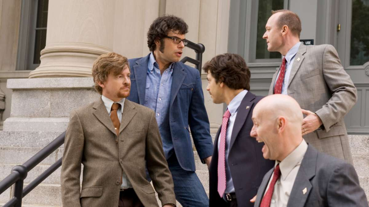 Murray and Jemaine stare off with men on steps