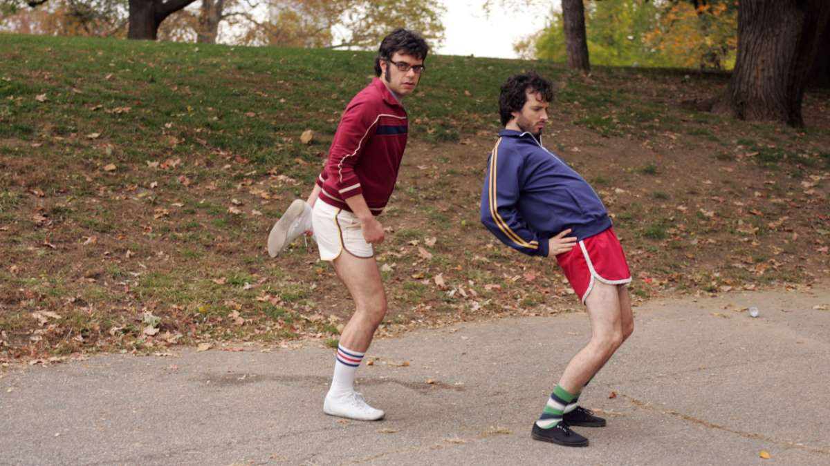 Jemaine and Bret stretch before running in the park