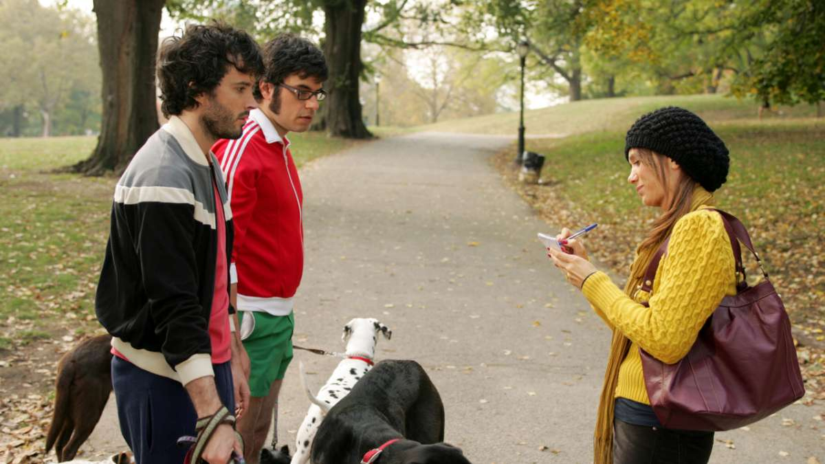 Bret and Jemaine with dogs speak to woman in park