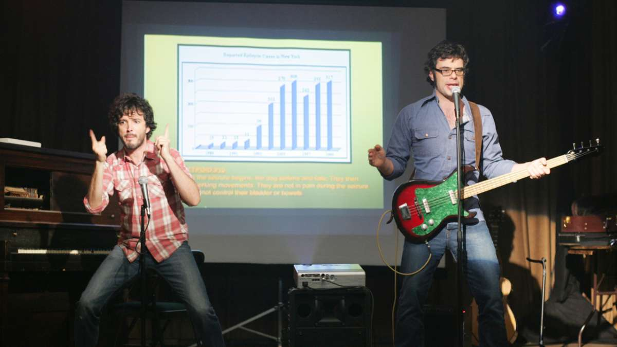 Bret an Jemaine perform with bar graph projection behind them