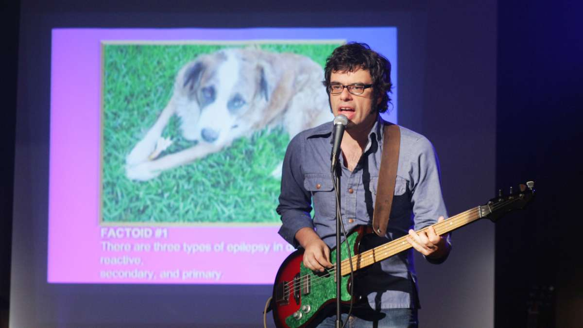 Jemaine sings with slide projection behind him