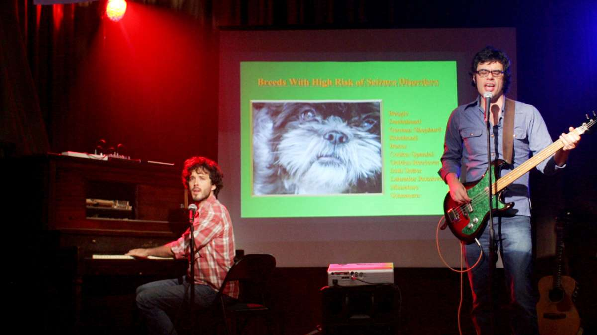 Jermaine Clement and Brent McKenzie perform in front of dog slideshow