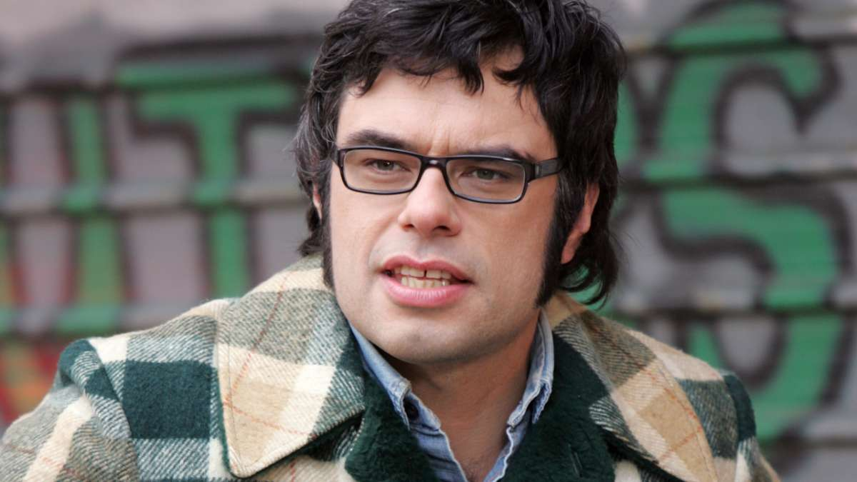 Jemaine stares left outside in plaid jacket