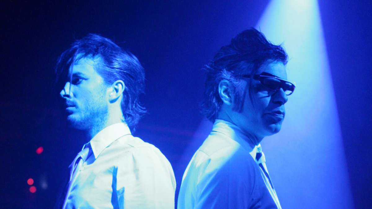 Bret and Jemaine in new wave outfits under blue light