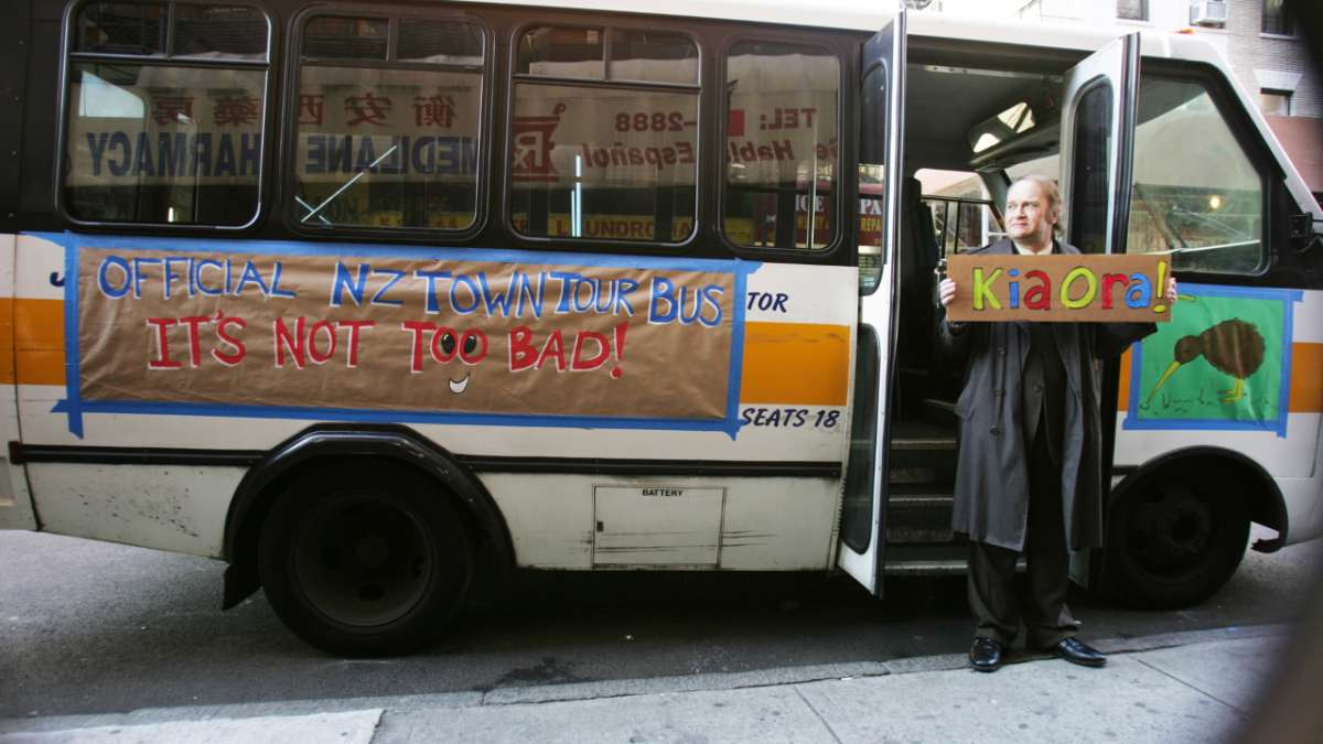 Prime minister holds sign in front of tour bus