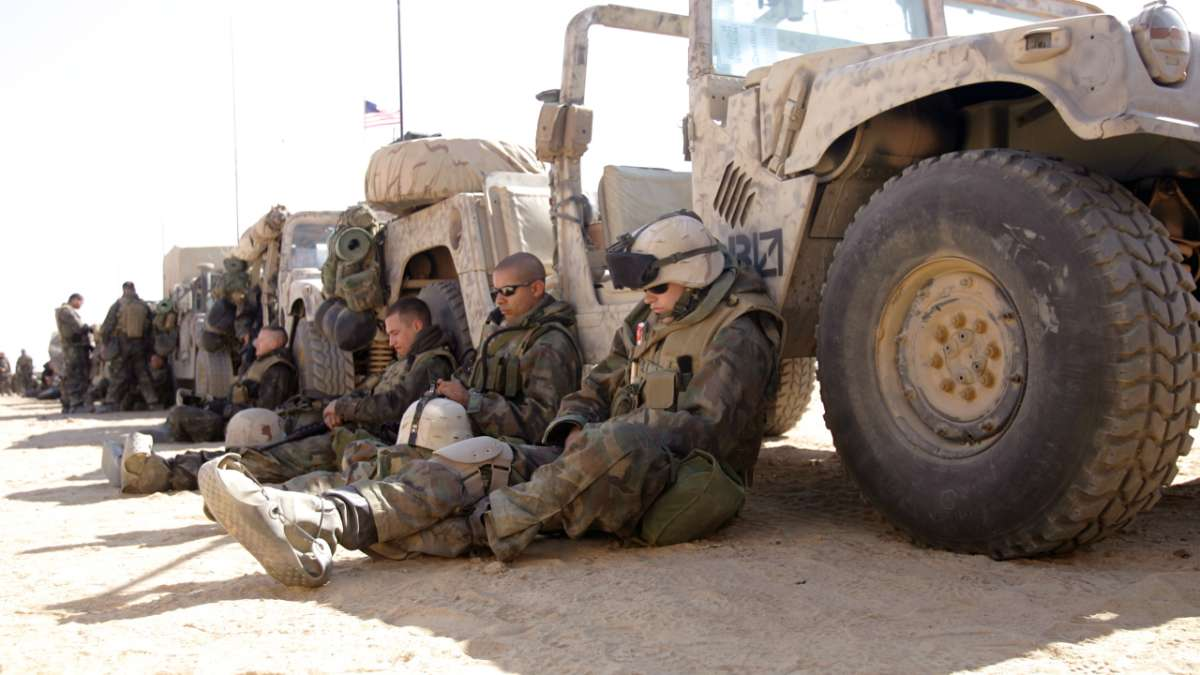 Marines sit in shade of humvees