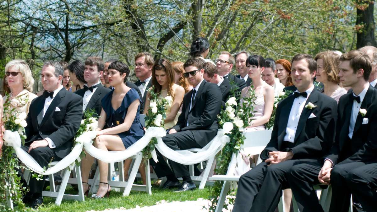 Ben and Rachel seated with others at wedding