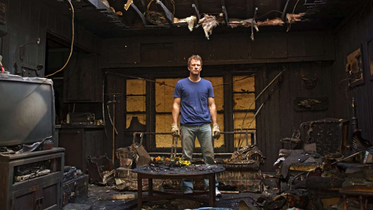 Ray standing in burned house
