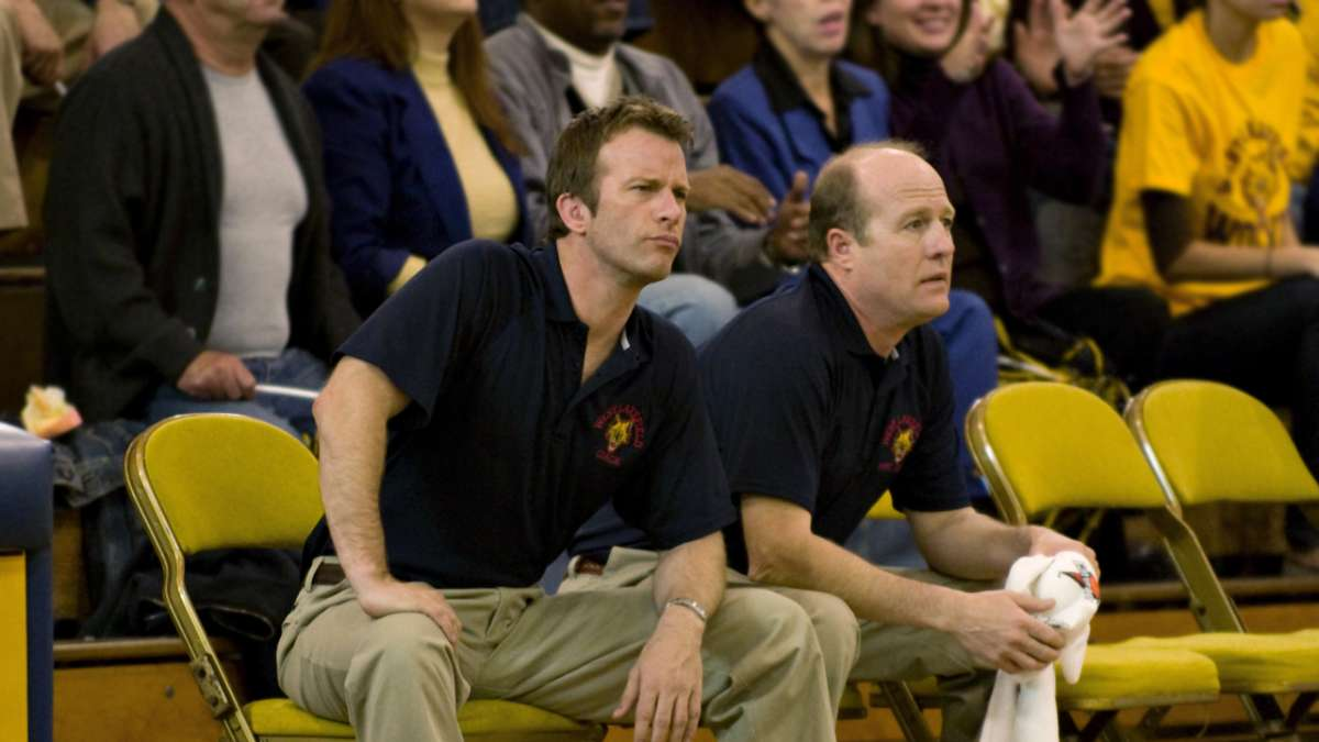 Ray seated with assistant coach at game