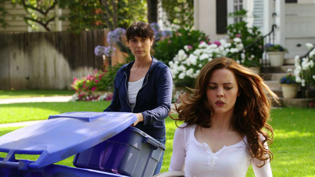 Laura walks away while Kate empties recycling