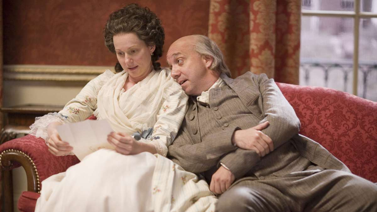 John Adams leans on Abigail Adams on couch