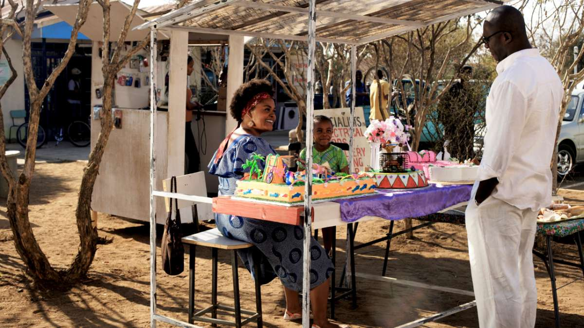 Precious Ramotswe sits at table with cakes looks at man in white