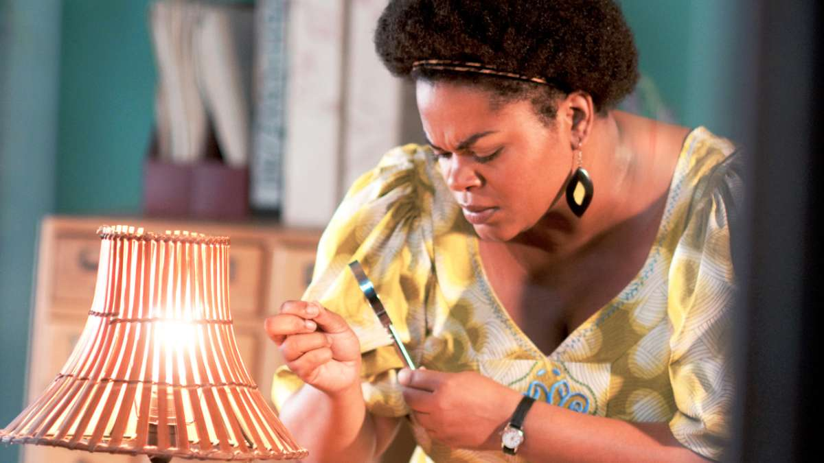 Precious Ramotswe inspects something with magnifying glass