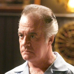 Paulie Walnuts close up leaning on bar