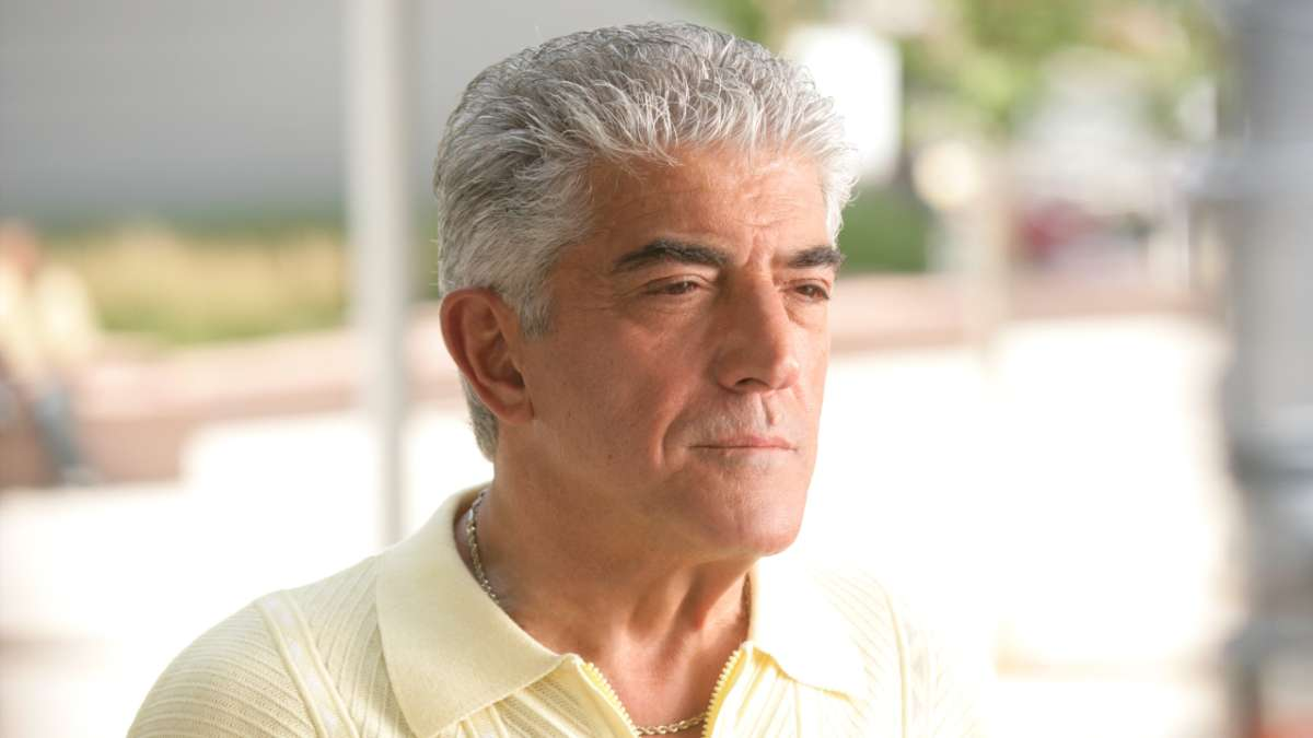 Phil Leotardo outside leaning on brick wall